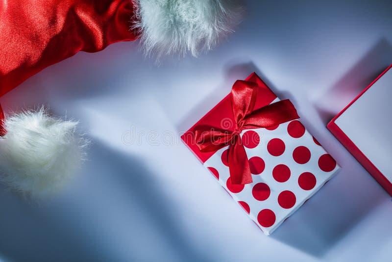 Το Santa ΚΑΠ τύλιξε το παρόν κιβώτιο στην άσπρη επιφάνεια στοκ φωτογραφία με δικαίωμα ελεύθερης χρήσης