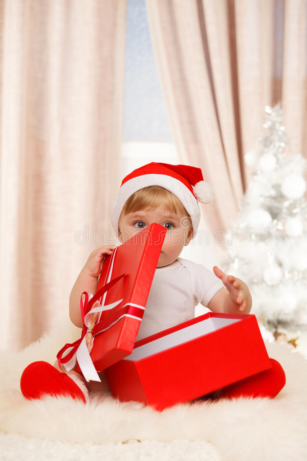 Το santa μωρών κρατά ένα μεγάλο κόκκινο κιβώτιο δώρων στοκ εικόνα