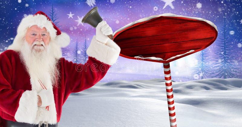Το Santa που κρατά ένα κουδούνι και ξύλινος καθοδηγεί στο χειμερινό τοπίο Χριστουγέννων στοκ εικόνα με δικαίωμα ελεύθερης χρήσης