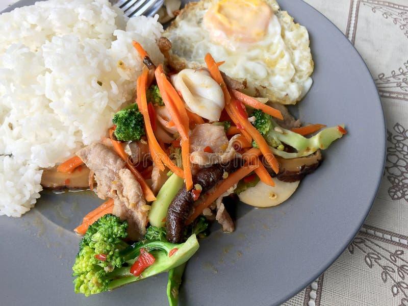 Το Sauteed ανάμιξε τη σάλτσα στρειδιών λαχανικών ν με το ρύζι και τηγάνισε το αυγό στο άσπρο πιάτο τρόφιμα Ταϊλανδός στοκ εικόνες