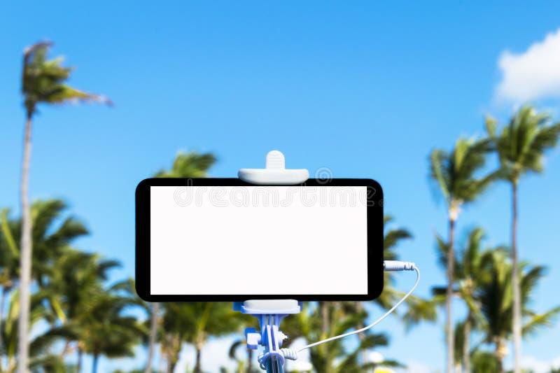 Το Selfie monopod κολλά με το κινητό τηλέφωνο, τροπικό υπόβαθρο, κενό διάστημα για το κείμενο, άσπρη οθόνη στοκ φωτογραφία με δικαίωμα ελεύθερης χρήσης