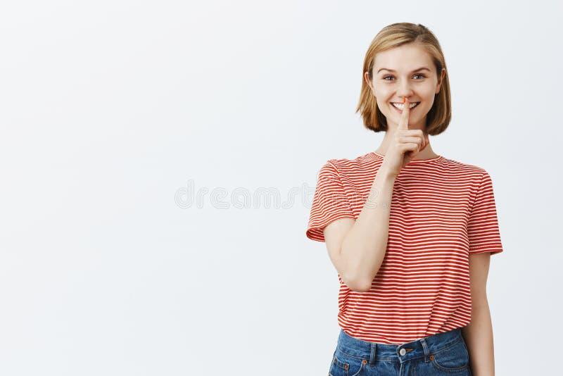 Το Shh, μυστικά πρέπει να κρατηθεί μέσα Ξένοιαστη ελκυστική γυναίκα στη ριγωτή μπλούζα, που παρουσιάζει shush χειρονομία με το δε στοκ εικόνες