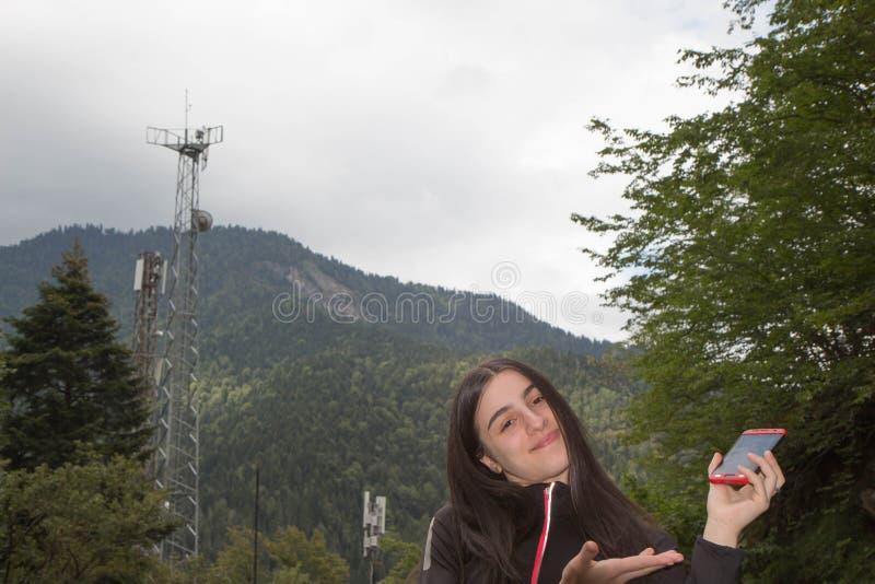 Το smartphone χρήσης κοριτσιών στην κεραία θόλωσε τις εικόνες στο ραδιο ιστό πύργων επικοινωνίας ή ηλεκτρικής ενέργειας με την εν στοκ εικόνες με δικαίωμα ελεύθερης χρήσης