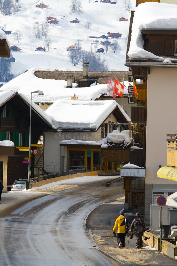 Το Snowboarders πηγαίνει κατά μήκος της οδού σε Grindelwald στοκ εικόνα