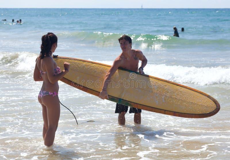 Το Surfer εξηγεί τη θεωρία του σερφ σε μια νέα γυναίκα στοκ εικόνες