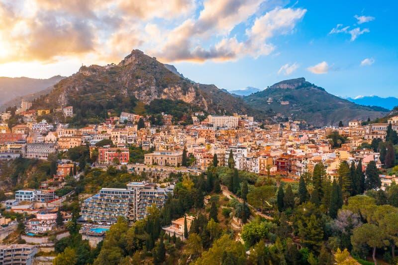 Το Taormina είναι μια πόλη στο νησί της Σικελίας, Ιταλία Εναέρια άποψη άνωθεν το βράδυ που μετριάζει στο πόδι των βουνών στοκ εικόνες