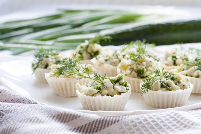Το Tartlets με το τυρί και την πράσινη πλήρωση κρεμμυδιών διακόσμησε με τον άνηθο σε ένα πιάτο στοκ φωτογραφία