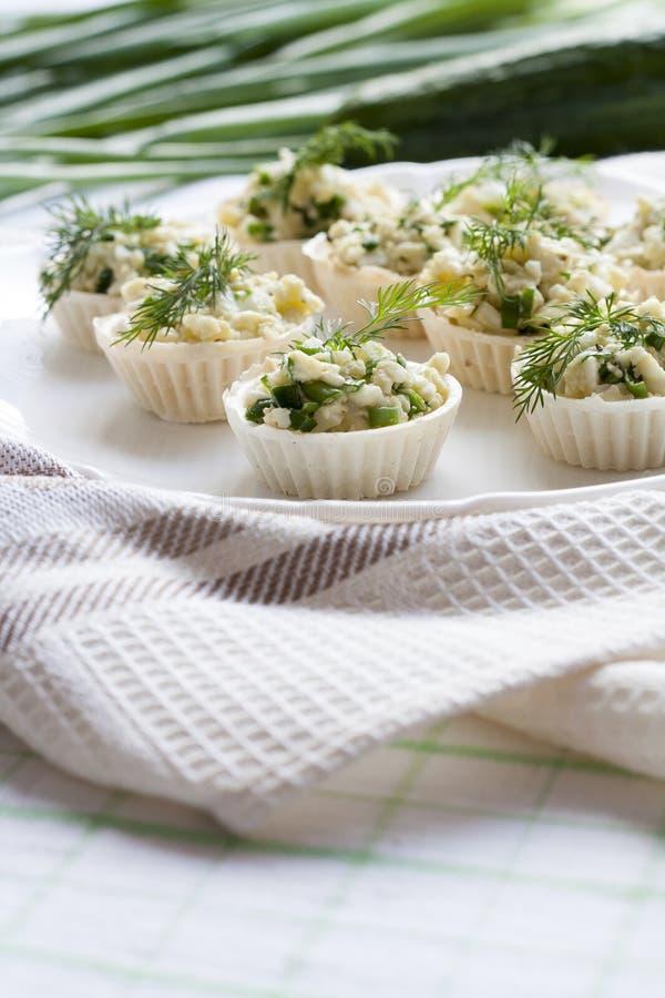 Το Tartlets με το τυρί και την πράσινη πλήρωση κρεμμυδιών διακόσμησε με τον άνηθο σε ένα πιάτο στοκ φωτογραφίες με δικαίωμα ελεύθερης χρήσης