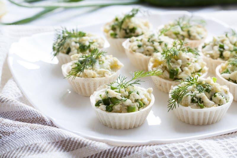 Το Tartlets με το τυρί και την πράσινη πλήρωση κρεμμυδιών διακόσμησε με τον άνηθο σε ένα πιάτο στοκ φωτογραφία με δικαίωμα ελεύθερης χρήσης