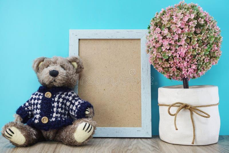 Το Teddy αντέχει και χωρίζει κατά διαστήματα το πλαίσιο φωτογραφιών με την τεχνητή εγχώρια διακόσμηση εγκαταστάσεων στο μπλε στοκ φωτογραφίες