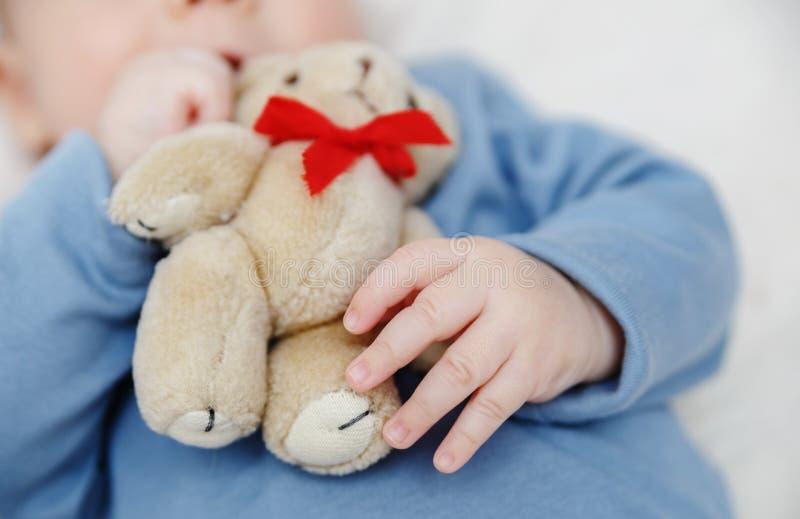 Το Teddy αντέχει στο χέρι μωρών στοκ φωτογραφίες με δικαίωμα ελεύθερης χρήσης