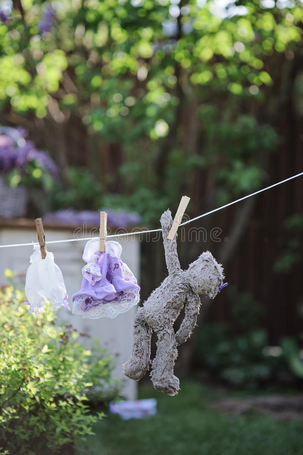 Το Teddy αντέχουν και τα φορέματα κουκλών που ξεραίνουν στο σχοινί στο θερινό κήπο στοκ φωτογραφίες