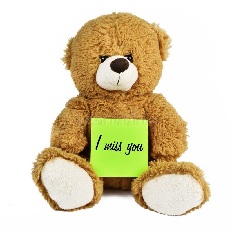 Το Teddy αφορά απομονωμένος το λευκό που κρατά ένα μήνυμα στοκ εικόνα