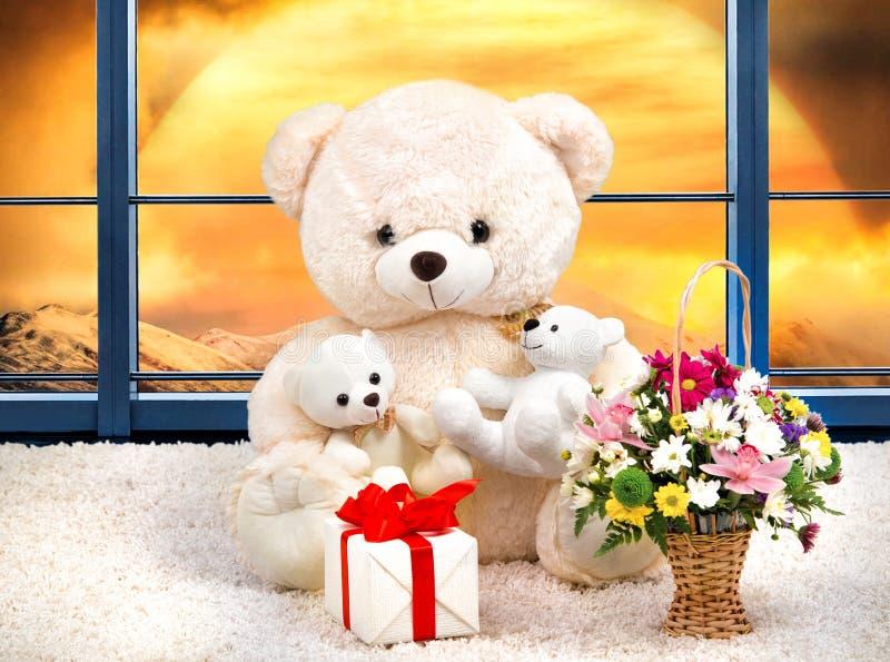 Το Teddy αφορά και καλάθι με τα λουλούδια το υπόβαθρο του ηλιοβασιλέματος Τα πανοραμικά παράθυρα στοκ φωτογραφία