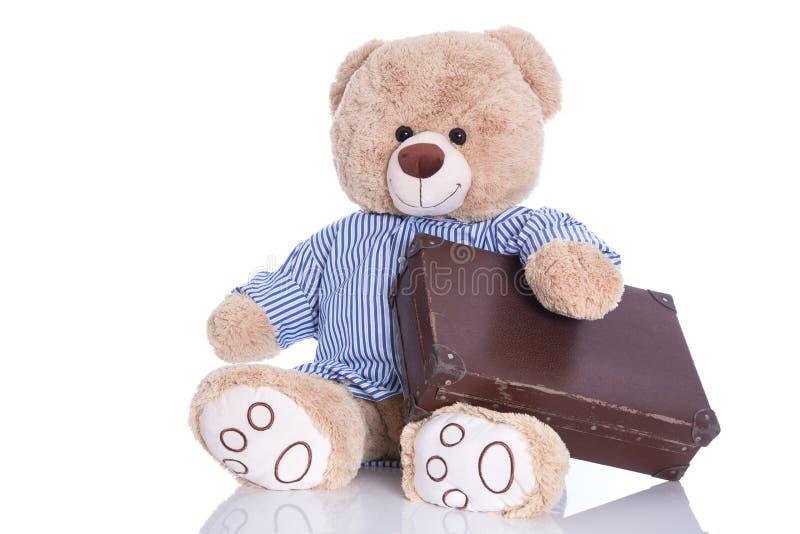 Το Teddy αφορά με τη βαλίτσα που απομονώνεται το άσπρο υπόβαθρο - sabbatic στοκ εικόνες