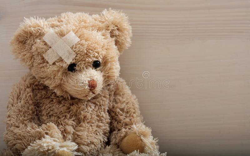 Το Teddy αφορά με τον επίδεσμο ένα ξύλινο πάτωμα στοκ φωτογραφία με δικαίωμα ελεύθερης χρήσης
