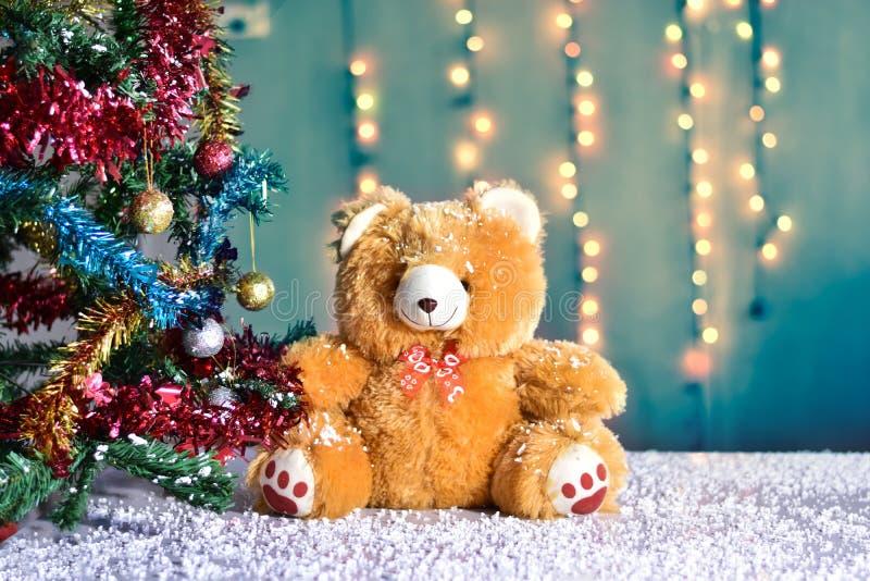 Το Teddy αφορά στα Χριστούγεννα και τις πολυ χρωματισμένες σφαίρες το χριστουγεννιάτικο δέντρο στοκ εικόνες