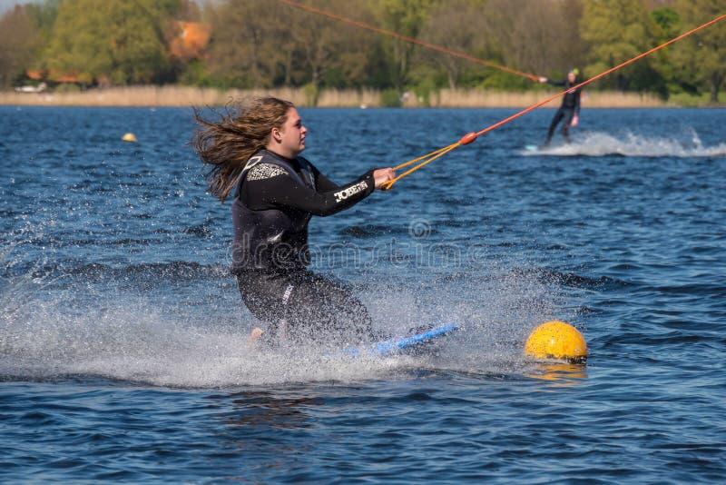 Το Wakeboarder κάνει το τέχνασμά της στη διαδρομή Wakeboard στοκ φωτογραφίες