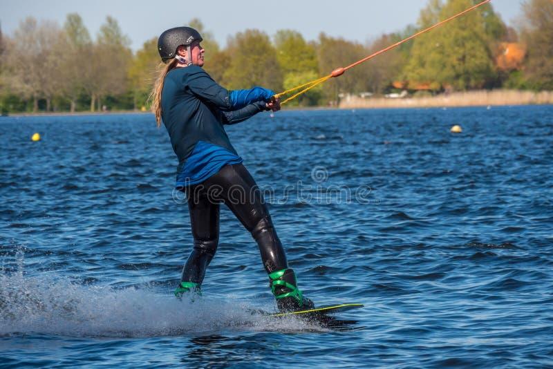 Το Wakeboarder κάνει το τέχνασμά της στη διαδρομή Wakeboard στοκ εικόνες