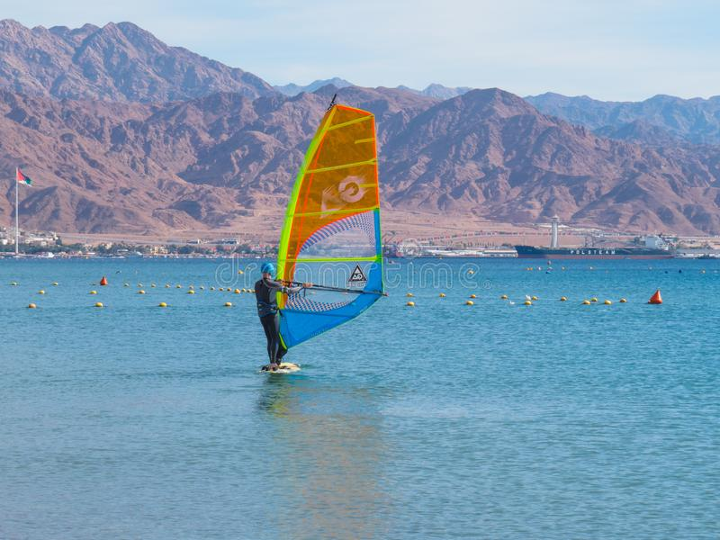 Το Windsurfer στον πίνακα με ένα πανί κινείται στη Ερυθρά Θάλασσα Υπόβαθρο - βουνά στοκ φωτογραφίες