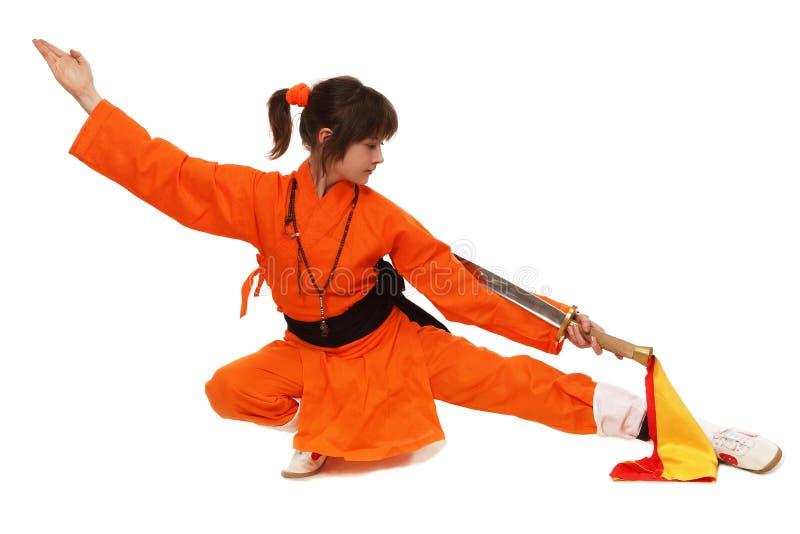 Το wushu κοριτσιών στο πορτοκαλί κοστούμι στη χαμηλή φρουρά στοκ εικόνες