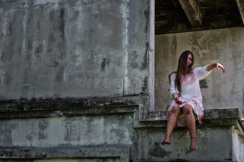 Το Zombie, φάντασμα, δολοφονία γυναικών με αιματηρό κάθεται την αναμονή για τη βοήθεια στοκ εικόνες
