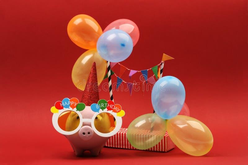 Τράπεζα Piggy με τα γυαλιά ηλίου χρόνια πολλά, το καπέλο κομμάτων και τα πολύχρωμα μπαλόνια κομμάτων στο κόκκινο υπόβαθρο στοκ εικόνες