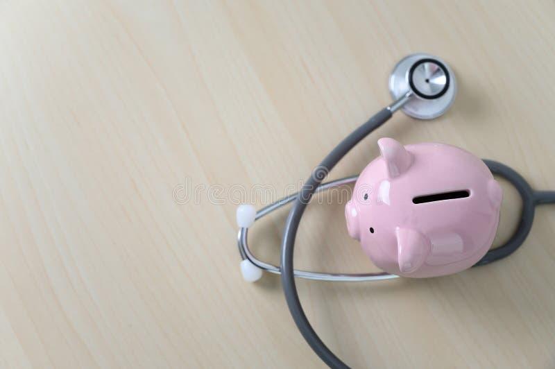 Τράπεζα Piggy με την οικονομική εξέταση ή την αποταμίευση στηθοσκοπίων για τις δαπάνες ιατρικής ασφάλειας στοκ φωτογραφία με δικαίωμα ελεύθερης χρήσης
