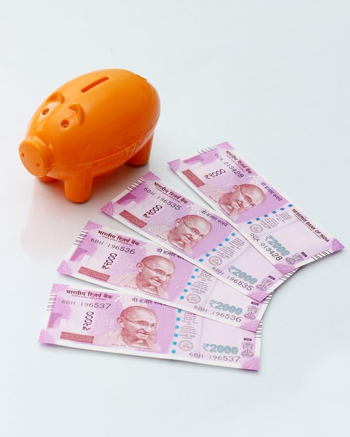 Τράπεζα Piggy με τις νέες σημειώσεις ρουπίων του 2000 για το άσπρο υπόβαθρο στοκ εικόνες με δικαίωμα ελεύθερης χρήσης