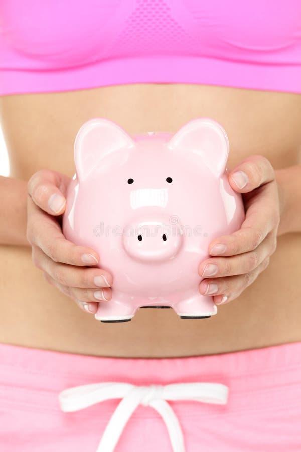 Τράπεζα Piggy μπροστά από το στομάχι στοκ εικόνα