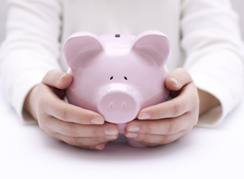 Τράπεζα Piggy που προστατεύεται με το χέρι στοκ εικόνες