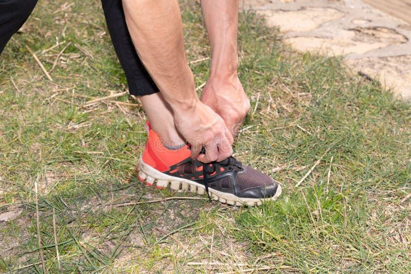 Τρέξιμο των δένοντας δαντελλών γυναικών δρομέων παπουτσιών κατά τη διάρκεια της jogging άσκησης κοριτσιών για το ρείκι και την ικ στοκ εικόνες