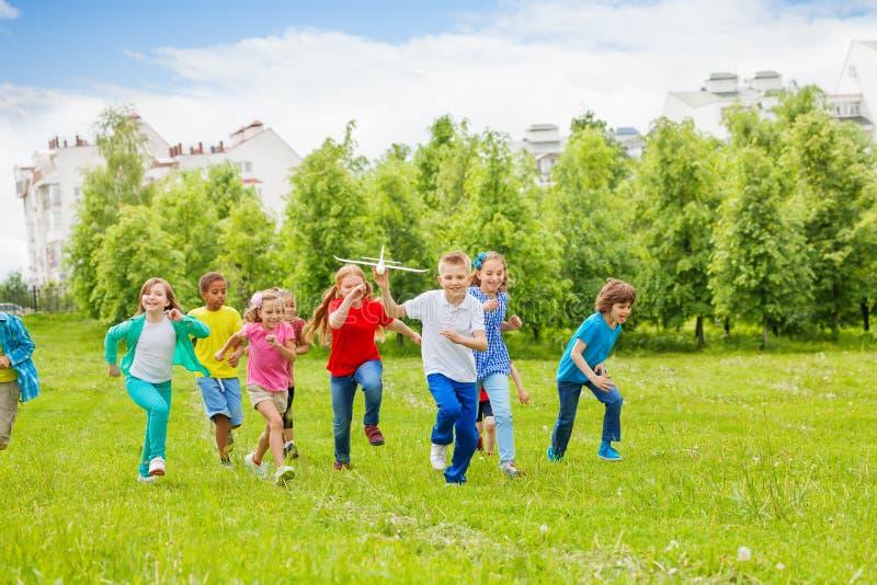 Τρέχοντας αγόρι με το παιχνίδι αεροπλάνων και παιδιά πίσω στοκ εικόνες