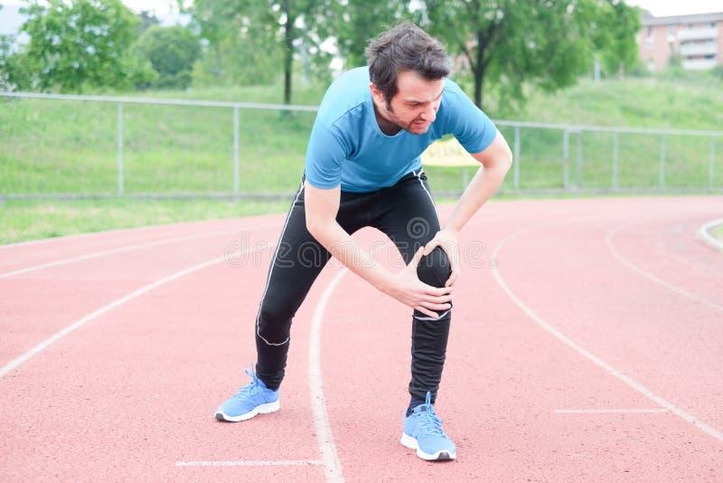 Τρέχοντας αθλητής που αισθάνεται τον πόνο λόγω του τραυματισμένου ποδιού στοκ φωτογραφία