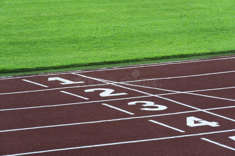 Τρέχοντας αθλητικό κομμάτι για τον αθλητή με τους αριθμούς στην άσπρη γραμμή έναρξης και το πράσινο υπόβαθρο αθλητικών σταδίων χλ στοκ εικόνες με δικαίωμα ελεύθερης χρήσης