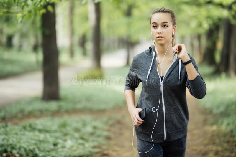 τρέχοντας γυναίκα Θηλυκός δρομέας Jogging κατά τη διάρκεια υπαίθριου Workout σε ένα πάρκο με τη μουσική στο ακουστικό από το τηλέ στοκ φωτογραφία με δικαίωμα ελεύθερης χρήσης