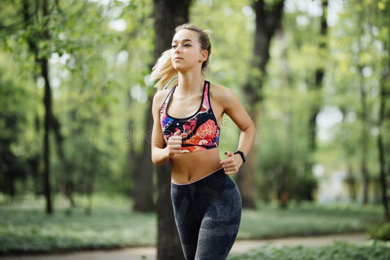 τρέχοντας γυναίκα Θηλυκό δρομέων κατά τη διάρκεια του υπαίθριου workout σε ένα πάρκο Όμορφο κατάλληλο κορίτσι μοντέλο ικανότητας  στοκ φωτογραφίες με δικαίωμα ελεύθερης χρήσης