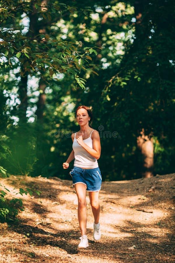 τρέχοντας γυναίκα πάρκων στοκ εικόνα με δικαίωμα ελεύθερης χρήσης