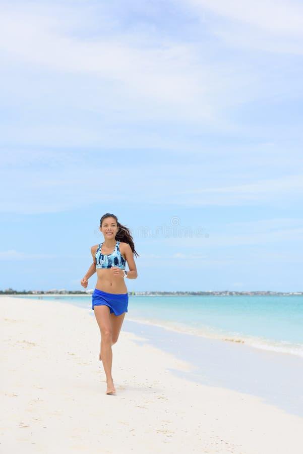 Τρέχοντας γυναίκα παραλιών που κάνει το καρδιο workout πρωινού στοκ φωτογραφία