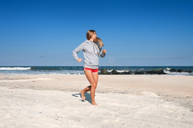 τρέχοντας γυναίκα παραλι Θηλυκό δρομέων στοκ εικόνες
