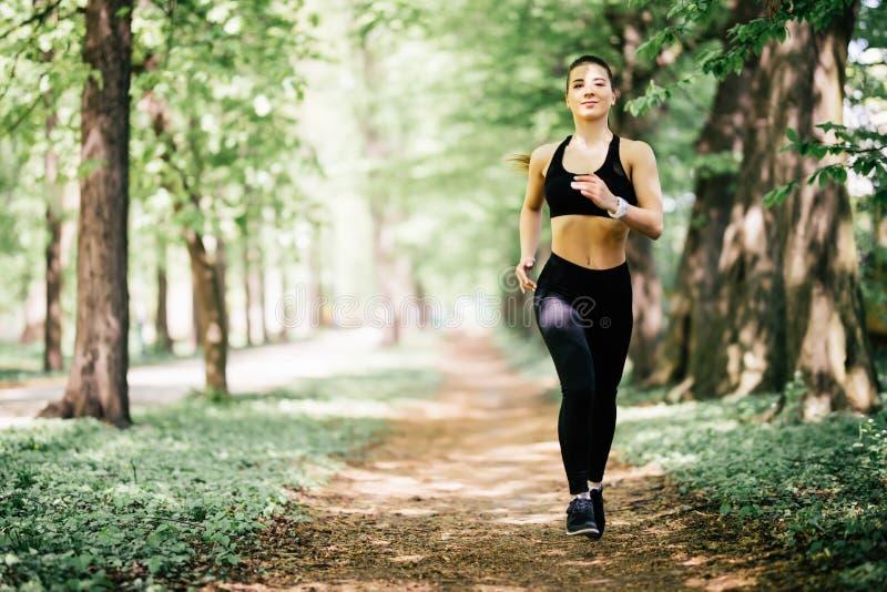 Τρέχοντας γυναίκα στο πάρκο Θηλυκό δρομέων κατά τη διάρκεια του υπαίθριου workout σε ένα πάρκο στοκ εικόνες