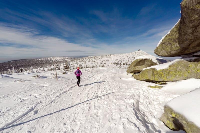 Τρέχοντας γυναίκα στο χειμερινό ίχνος, το χιόνι και τα άσπρα βουνά στοκ εικόνα