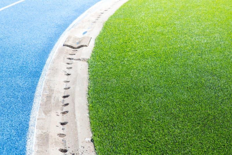 Τρέχοντας διαδρομή με τον τομέα χλόης ποδοσφαίρου στοκ εικόνες