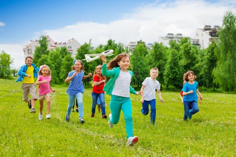 Τρέχοντας παιχνίδι και παιδιά αεροπλάνων εκμετάλλευσης κοριτσιών πίσω στοκ εικόνες
