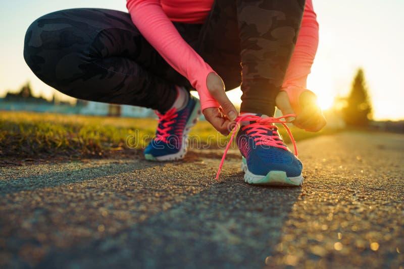 Τρέχοντας παπούτσια - δένοντας δαντέλλες παπουτσιών γυναικών στοκ εικόνα με δικαίωμα ελεύθερης χρήσης