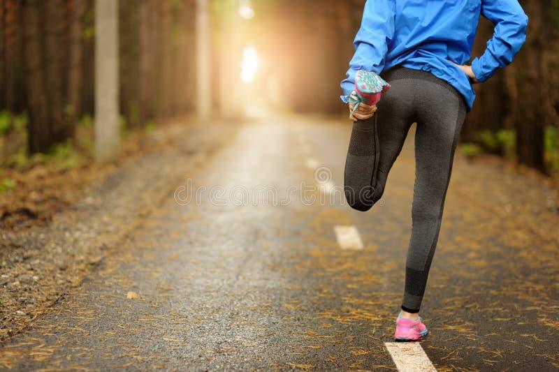 Τρέχοντας δρομέας τεντώματος που κάνει την προθέρμανση πριν από το μαραθώνιο στοκ φωτογραφία