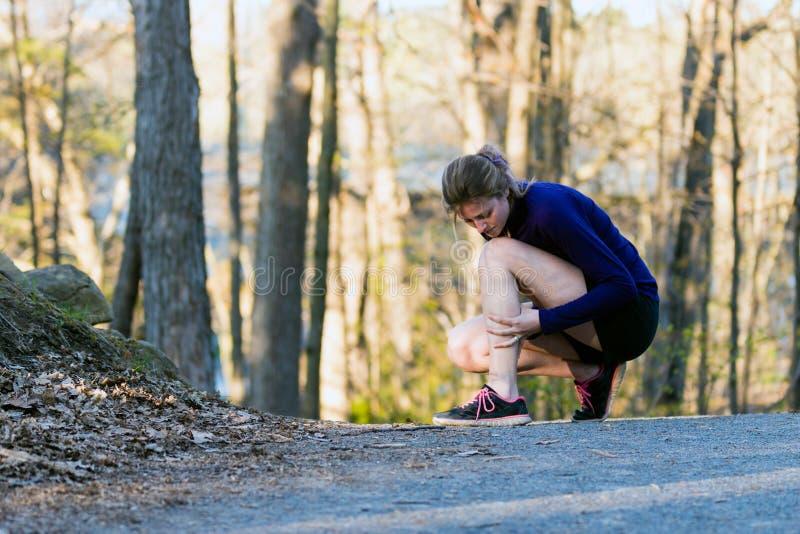 Τρέχοντας τραυματισμός ναρθήκων αντικνημίων για νέο γυναικών στο tra φύσης στοκ εικόνες