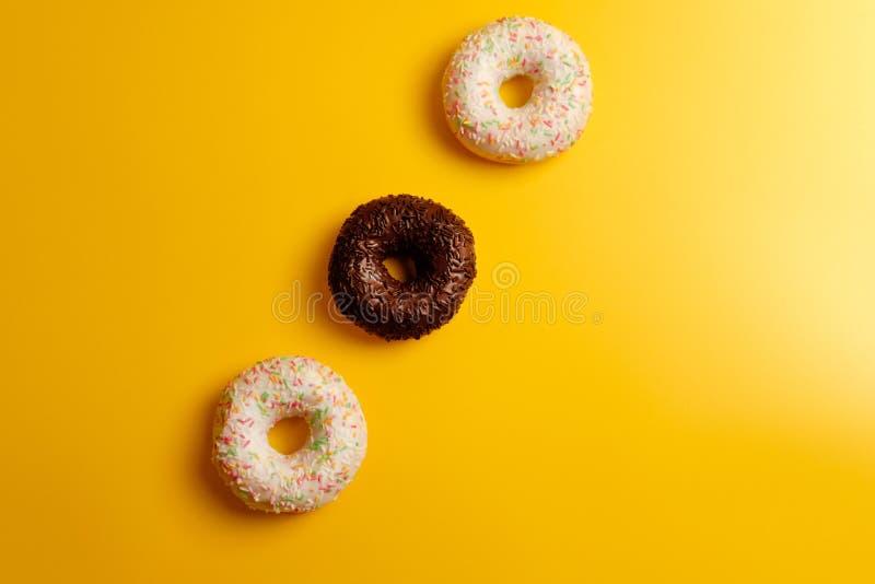 Τρία άσπρα και μαύρα donuts στην κίτρινη τοπ άποψη υποβάθρου στοκ εικόνες με δικαίωμα ελεύθερης χρήσης