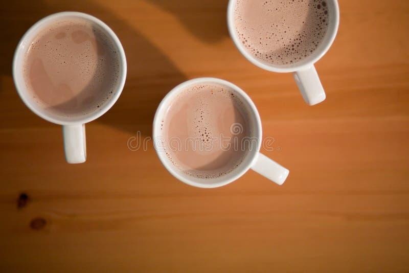 Τρία άσπρο φλυτζάνι του καυτού latte, καφές στον ξύλινο πίνακα στοκ φωτογραφίες