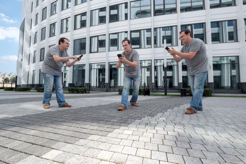 Τρία άτομα με ένα κινητό τηλέφωνο μπροστά από μια άσπρη επιχείρηση cente στοκ εικόνες με δικαίωμα ελεύθερης χρήσης